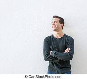 Young man standing against white background with arms crossed
