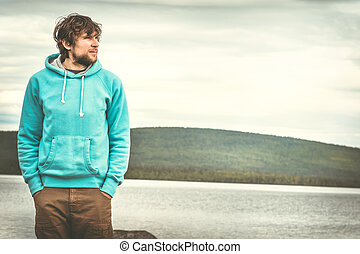 Young Man standing alone outdoor with scandinavian mountains...