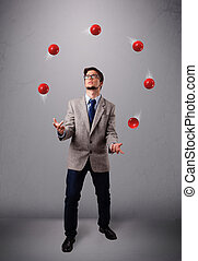 young man standing and juggling with red balls - handsome...
