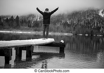 Young man standing at the end of wooden pier on a lake