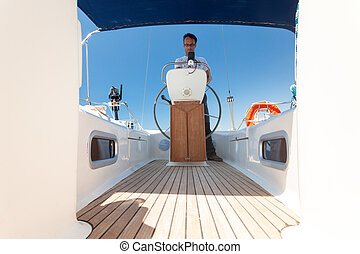 Young man standing at the helm of a boat against a blue sky