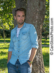 Young man standing at tree in park in summer - Young man ...