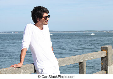 Young man standing by the sea