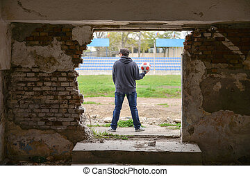 Young man standing in a old abandoned building with a soccer ball in his hand
