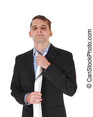 Young man standing in a suit fixing tie