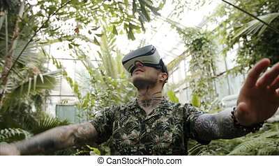Young man standing in botanical garden, using VR glasses. - ...