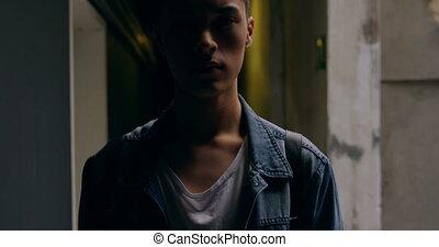 Young man standing in corridor 4k - Portrait of young man ...