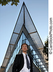 Young man standing in front of a modern building