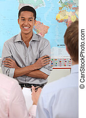 Young man standing in front of a world map