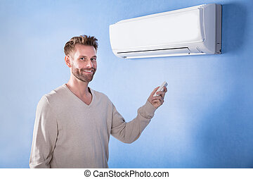 Young Man Standing In Front Of Air Condition