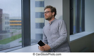 Young man standing in the corridor, holding a smart phone and looking out the window.