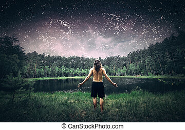 Young man standing in the forest at night.