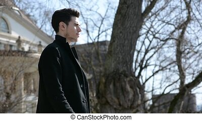 Attractive young man standing looking over landscape in a sunny day, thiinking with a serious expression, wearing winter coat
