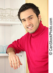 Young man standing next to a cupboard full of glasses