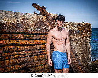 Young man standing next to rusty metal structure