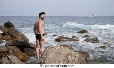 Young man standing on a beach alone