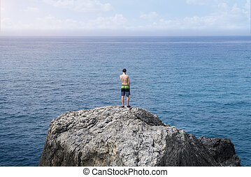 young man standing on a cliff
