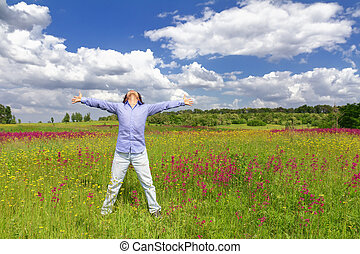 Young man standing on a meadow on a blue sky background