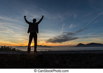 Young man standing on an old wall under glorious evening sky