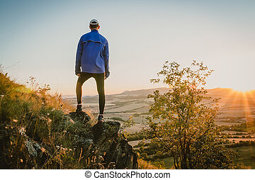 Young man standing on rock and looking to Czech ore mountain valley at sunrise. Czech landscape