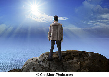 young man standing on rock mountain and looking to the sun ...