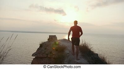 Young man standing on the edge of a cliff and meets the sun,...