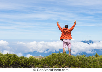 young man standing on the top of mountain