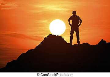 young man standing on the top of the mountain