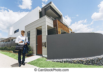Young man standing outside his modern house