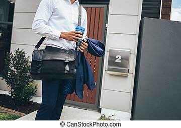 Young man standing outside his modern apartment