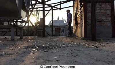Young man stands and calls on a construction site in slo-mo