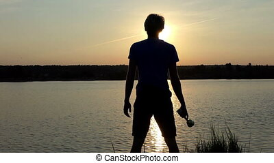 Young man stands and keeps a winner bowl at a lake in slo-mo