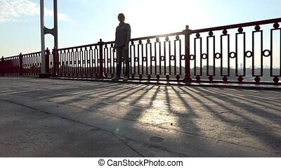 Young Man Stands Near Handrails of a Bridge Over the Dnipro at Sunset in Slo-Mo