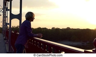 Young Man Stands on a Bridge Over The Dnipro River in Summer on a Sunny Day