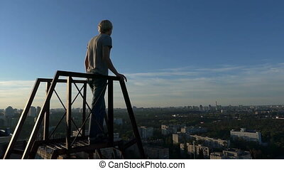 Young man stands on a metallic staircase on a high building in slo-mo
