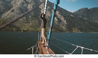 Young man stands on bowsprit of sailboat and screams outdoors.