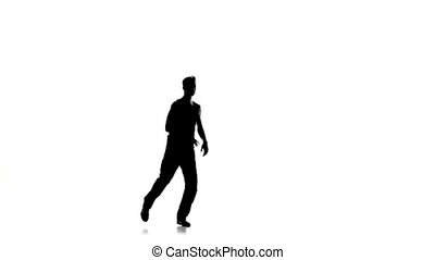 Young man stands on hands dancing breakdance, white, silhouette, slow motion