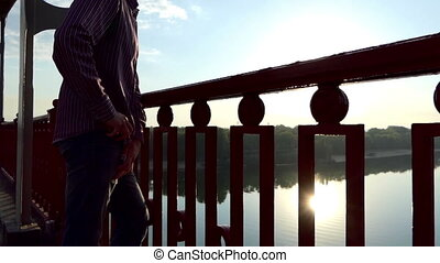 Young Man Stands on The Bridge And Pulls Out His Mobile at Sunset in Slo-Mo