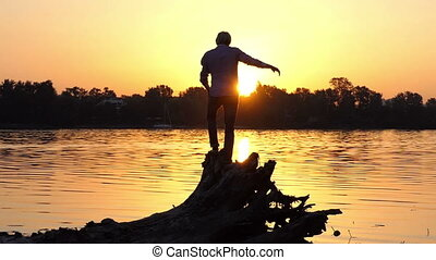 Young man stands on the tree roots on a lake bank in slo-mo