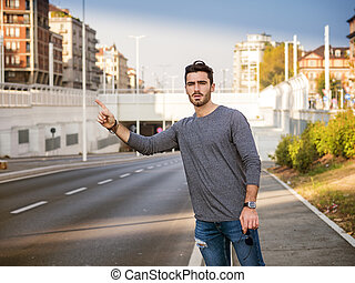 Young man stopping a taxi cab