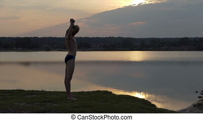 Young man stretches his shoulders on a lake bank in slo-mo