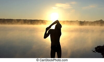 Young man stretches out his arms on a lake bank at sunset