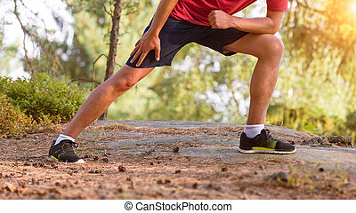 Young man stretching before jogging, cross country runner