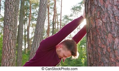 Young Man Stretching in the Forest