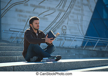 Young man studen reading book outdoors in sunny day