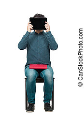 Young man student, seated on a chair, cover his head using a PC tablet, while holds a red book on his knees. Modern education concept. Study and work from home. Anonymous reader isolated on white.