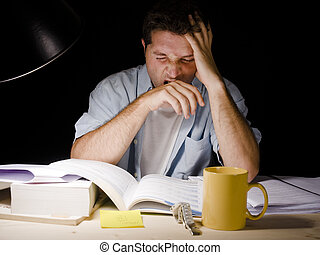 Young Man Studying at Night - Young Man Yawning tired while...