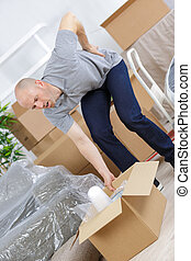 young man suffering from backpain while lifting carton