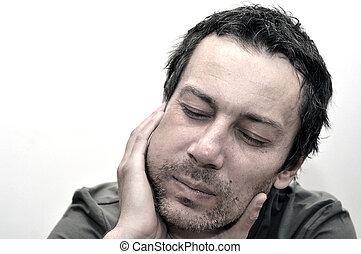 Young man suffering from toothache, teeth pain, swollen face