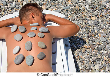young man sunbathes on beach with stones on back
